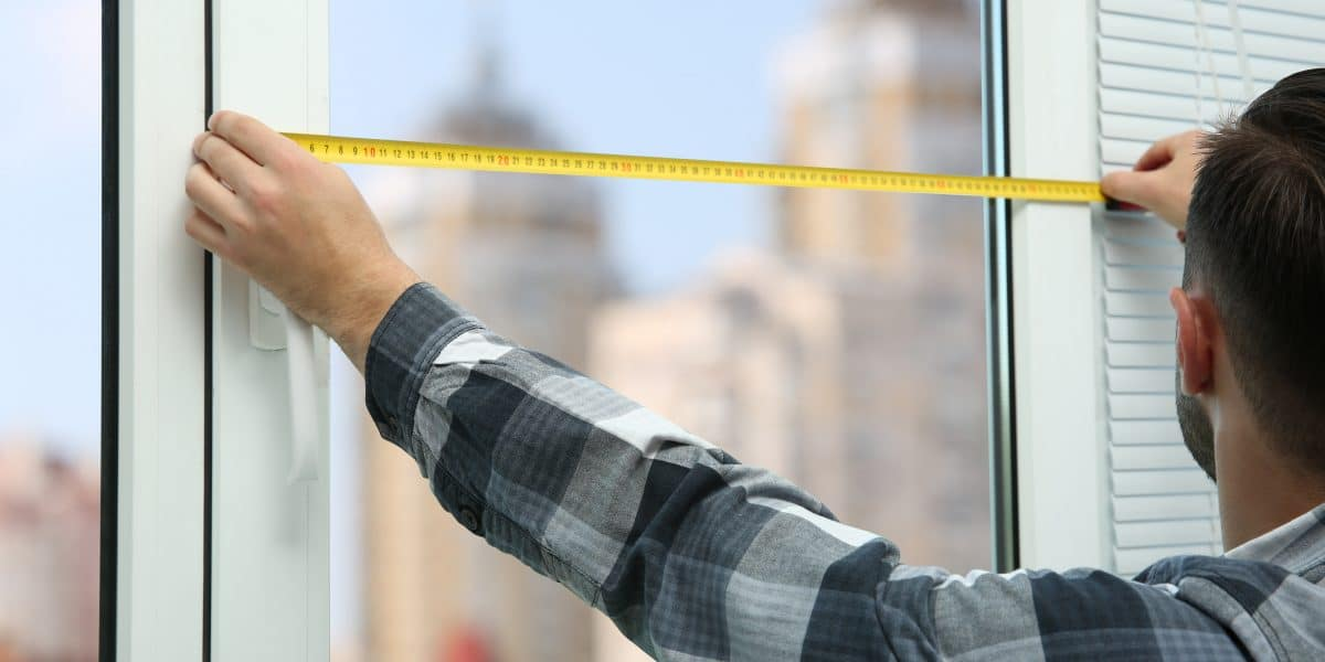 man measuring home for new windows